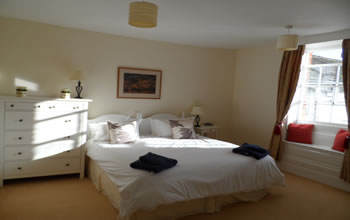 The master bedroom at Enford House cottage has views over the meadow and garden. Ensuite bathroom and facilities