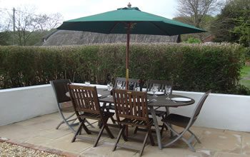 Enford House Cottage Self catering holiday cottage has a south facing terrace table which seats 6 people with a BBQ
